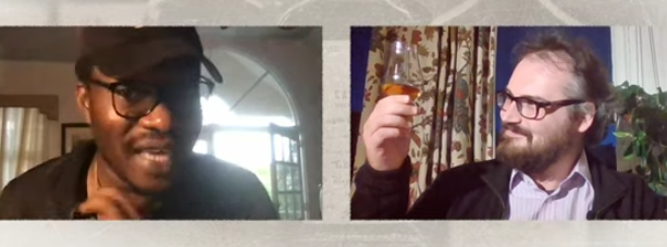 Two men excited to sample some rums. One holds a whisky glass in the air - it is full of rhum. They are having a Zoom tasting.