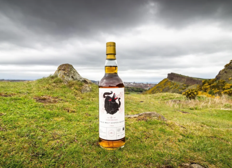 A bottle of whisky on a green hill under a dark sky
